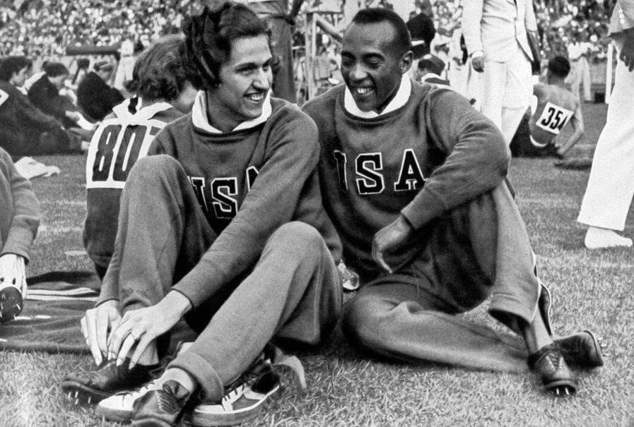 Helen Stephens and Jesse Owens, American athletes, Berlin Olympics, 1936. The two won six gold medals between them: Stephens in the women's 100 metres and 4x100 metres relay and Owens in the men's 100 metres, 200 metres, 4x100 metres and Long Jump. A print from Olympia 1936, Die Olympischen Spiele 1936, Volume II, Cigaretten-Bilderdienst, Hamburg, 1936. (Photo by The Print Collector/Print Collector/Getty Images)